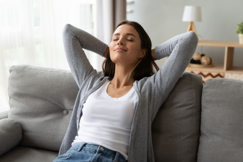 Negative Menschen: Frau sitzt entspannt auf dem Sofa.