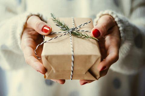 Eine Frau hält ein Geschenk in der Hand