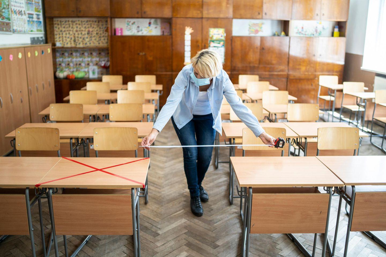 Lehrerin misst Abstand zwischen den Tischen