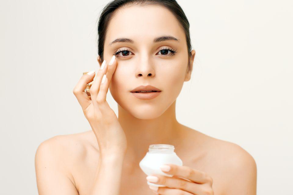 Schöne Frau mit reiner Haut trägt Augencreme auf