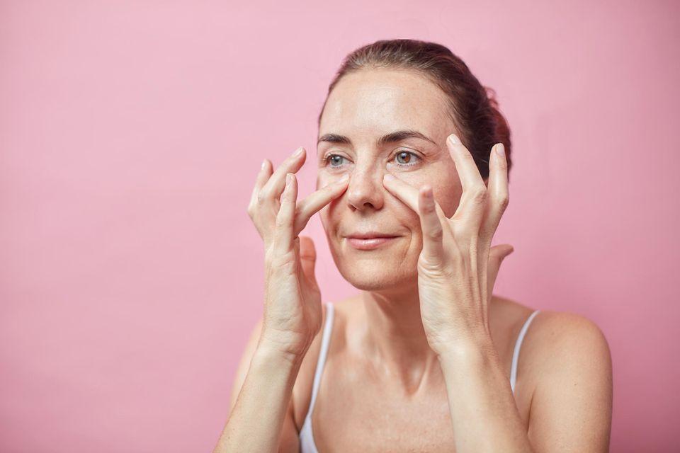 Frau trägt Augencreme vor pinkem Hintergrund auf