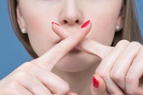 Tabuthemen: Frau verkreuzt Zeigefingern vor den Lippen