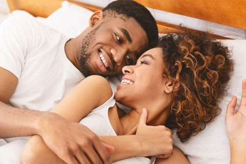 Sexstellung 77: Pärchen liegt im Bett und lächelt sich an