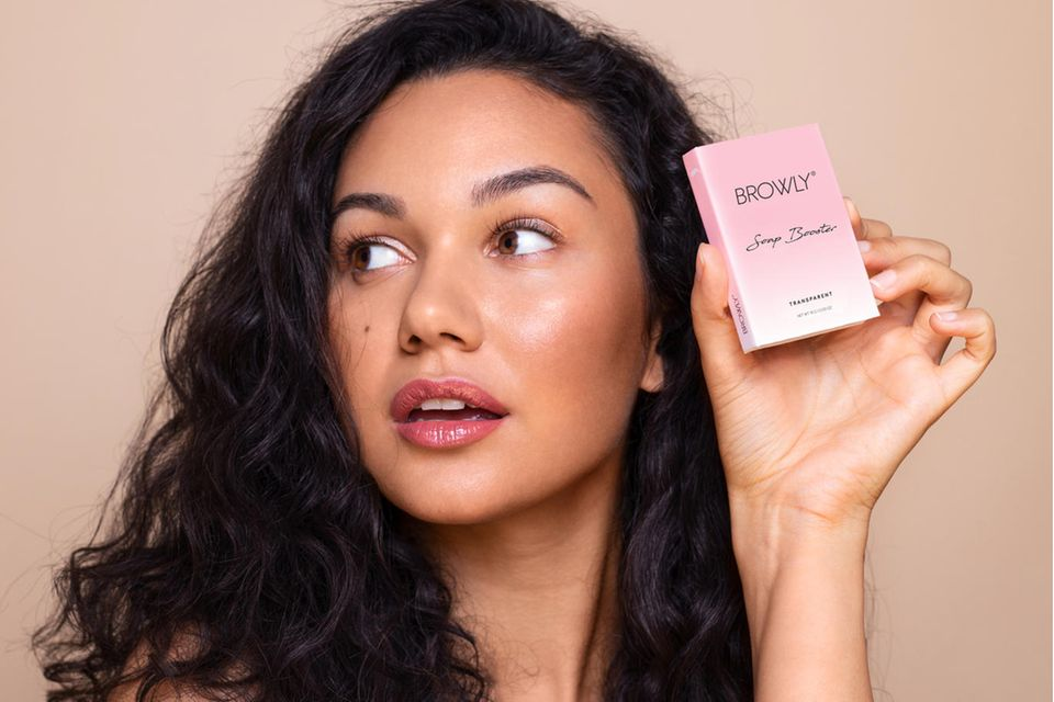 Brunette woman holds brow soap in her hand