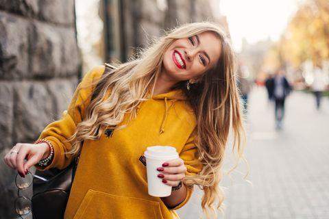 Resilienz stärken: Lächelnde Frau mit einem Kaffee in der Hand.