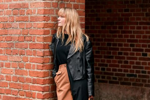 Pony-Frisur: Frau mit Pony lehnt an einer Mauer