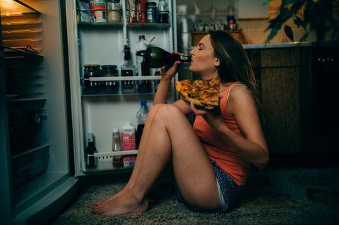 Frau sitzt vor Kühlschrank mit Pizza und Wein