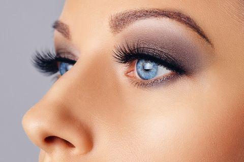 Blaue Augen mit dunkel geschminkten Augenlidern und langen Wimpern