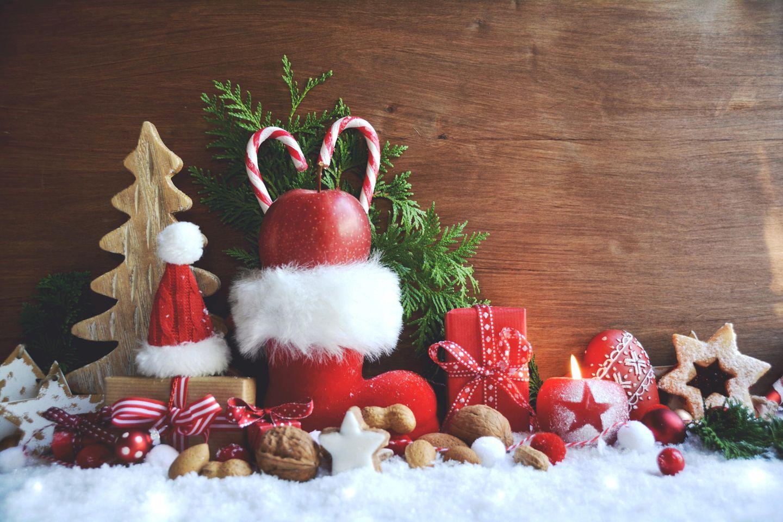 Nikolaus-Geschenkideen: roter Nikolausstiefel, Nüsse, Zimtsterne, Kunstschnee, Tannenzweig, kleine Geschenke, Weihnachtsdeko
