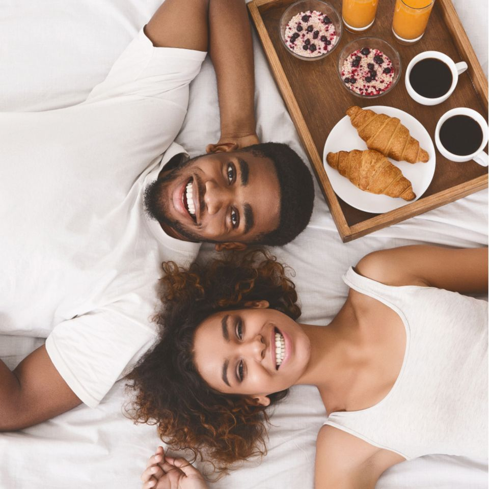 Frühstück im Bett: Pärchen liegt im Bett mit Frühstückstablett