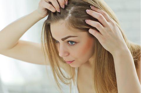 Haarausfall stoppen: Blonde Frau, die ihre Kopfhaut untersucht.
