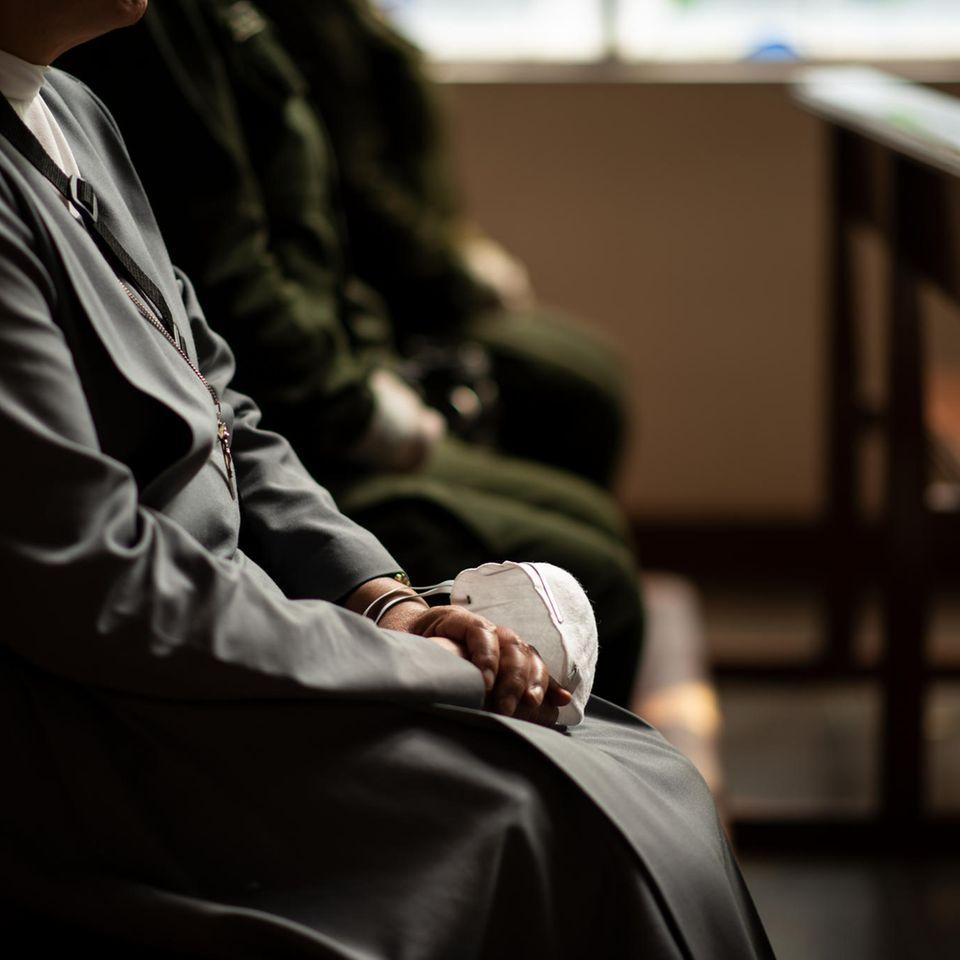 Corona aktuell: Nonne mit Maske auf dem Schoß in der Kirche