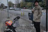 Abenteuerliche Babyfotos: Vater mit Kinderwagen im Regen