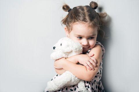Kuscheltier: Mädchen kuschelt mit Plüschtier
