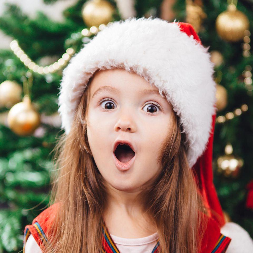 Tannenbaum: Überraschtes Kind mit Mütze