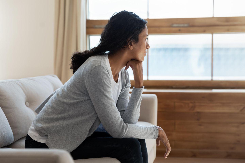 Selbstquarantäne vor Weihnachten: Frau schaut aus Fenster