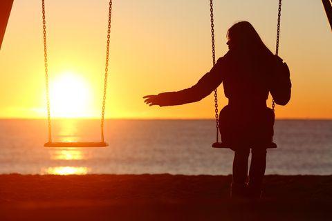 Frau einsam auf einer Schaukel