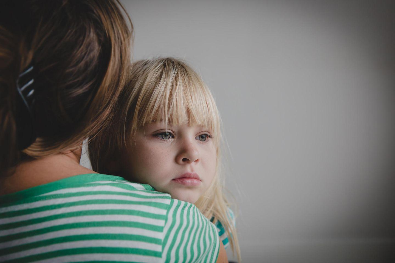 Kinder fördern: Trauriges Kind auf dem Arm der Mutter