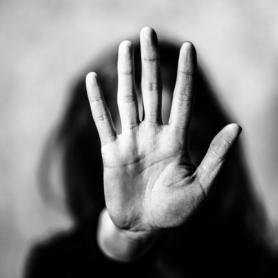 Frau hält eine Hand vor die Kamera