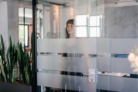 Impostor-Syndrom: Frau steht hinter Glastür