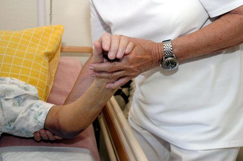 Corona aktuell: Pflegekraft hält alte Hand