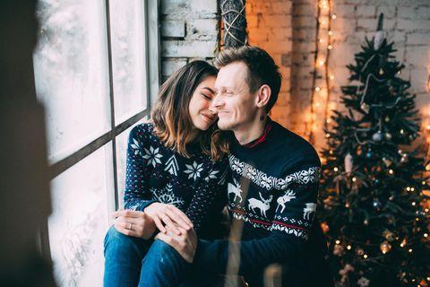 Horoskop: Liebeserklärung vor Weihnachten: Paar am Fenster