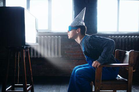 Verschwörungstheorien: Mann mit Aluhut und Plastikbrille vor Fernseher