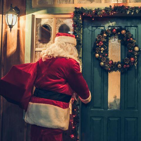 Weihnachtsmann mit Geschenken vorm Haus