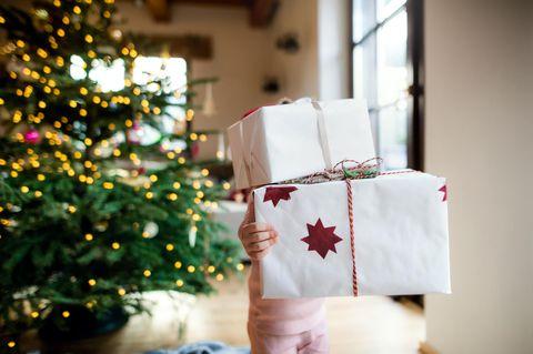 Kind trägt viele Geschenke