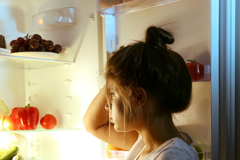 Hungergefühl: Frau vor offenem Kühlschrank