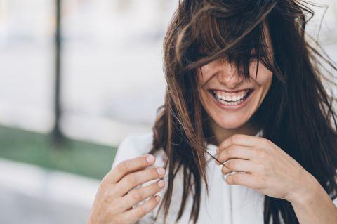 Lächelnde Frau mit zersträubten, braunen Haaren