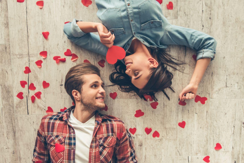 101 Gründe, warum ich dich liebe: Pärchen liegt auf dem Boden mit Papierherzen