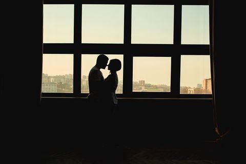 Liebesleben in Coronazeiten: Paar umarmt sich hinter Fensterscheiben