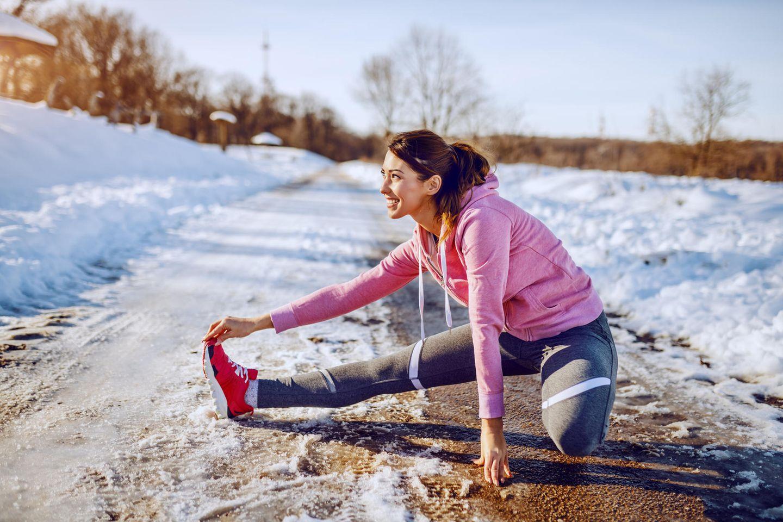 Sport im Winter: Frau dehnt sich im Sport