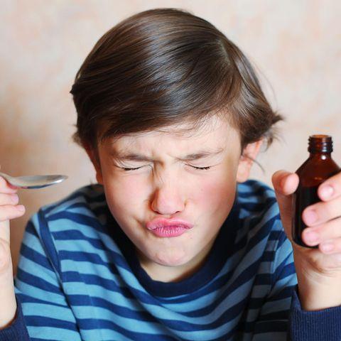 Das Kind will die Medizin nicht? Junge mit Löffel und Medizin in der Hand