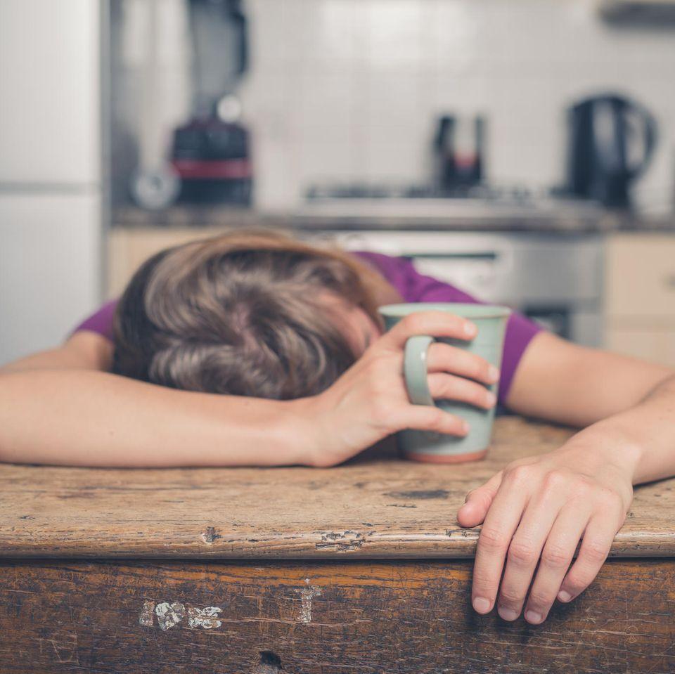 Narkolepsie: Frau schläft mit Tasse in der Hand auf dem Tisch