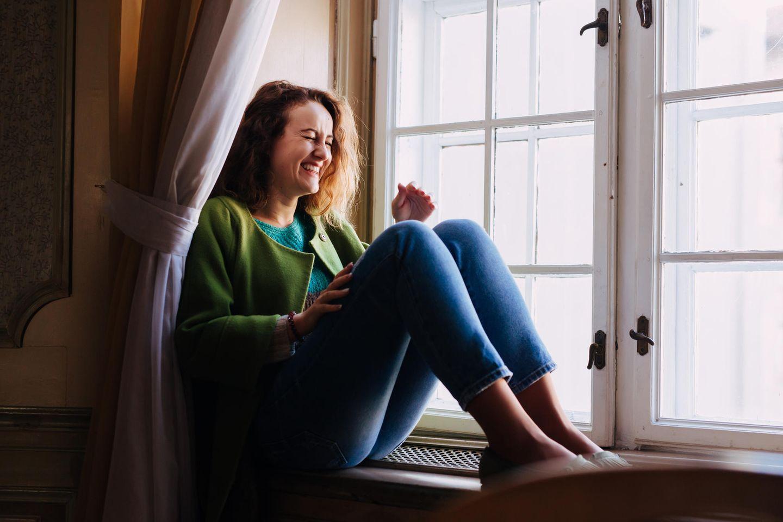 Terminkalender: Frau lachend auf Fensterbank