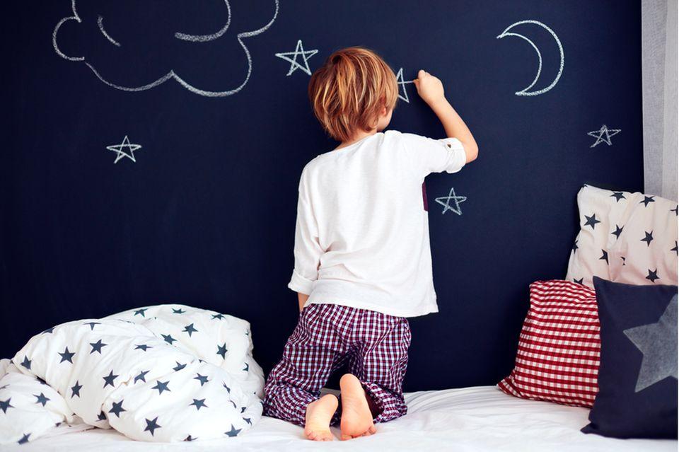 Kinderzimmer gestalten: Kind malt auf Tafel