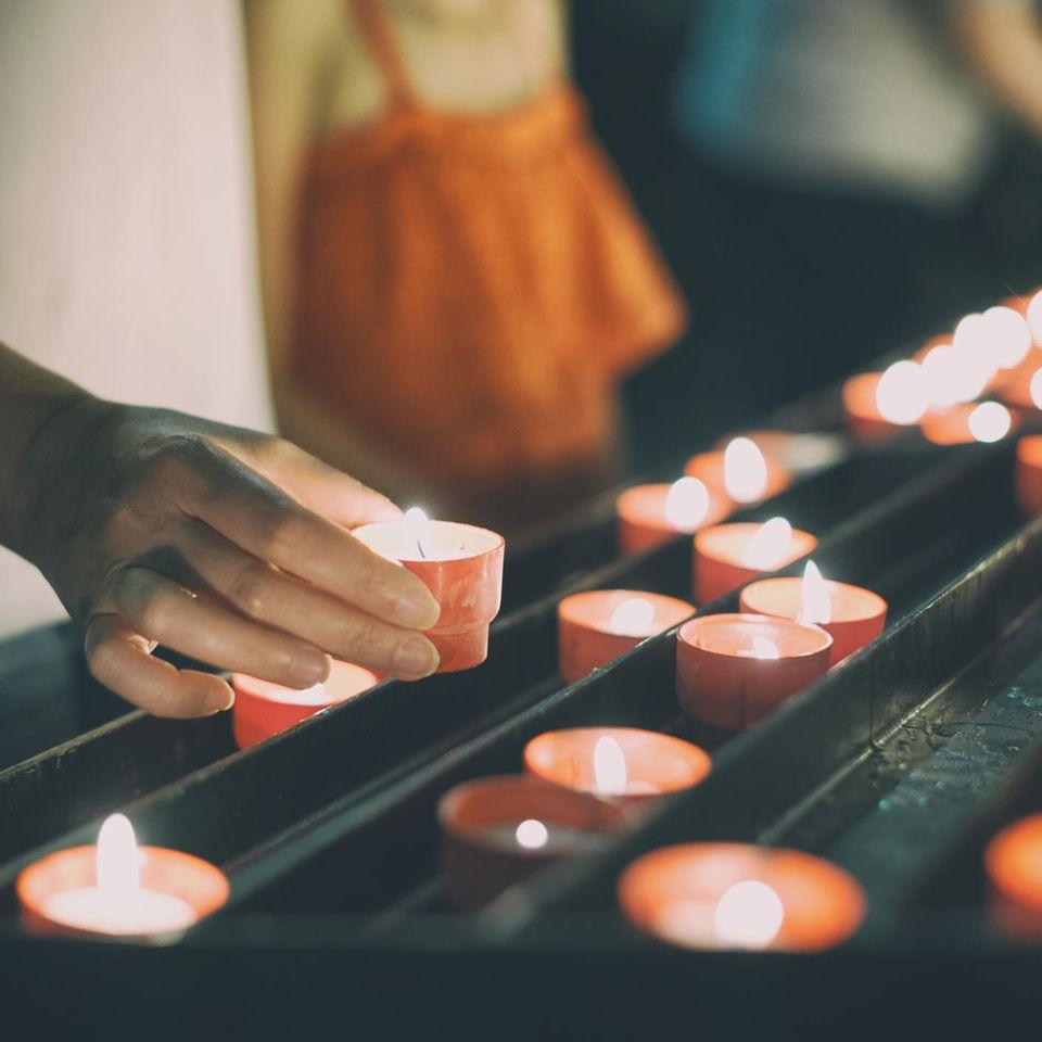 Tod des Partners: Person stellt brennende Kerze auf