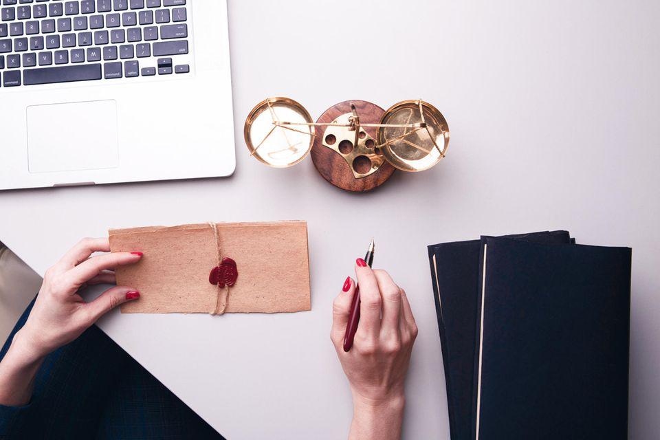 Jung verwitwet: Frau am Tisch mit Laptop und Notizbüchern