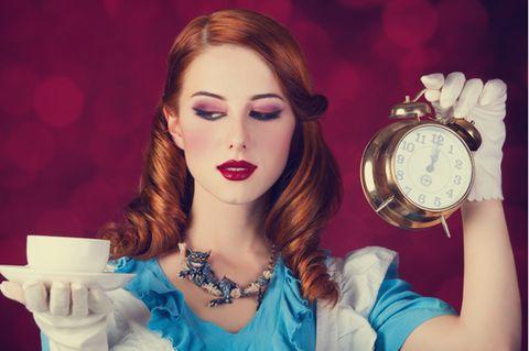 Kindheitshelden: Frau hält Uhr und Tasse