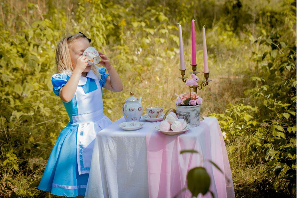 Kindheitshelden: Mädchen im Alice-im-Wunderland-Kostüm