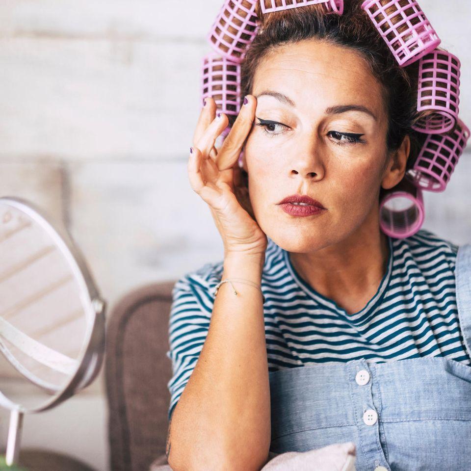 Midlife Crisis: Frau mit Lockenwicklern vor Spiegel