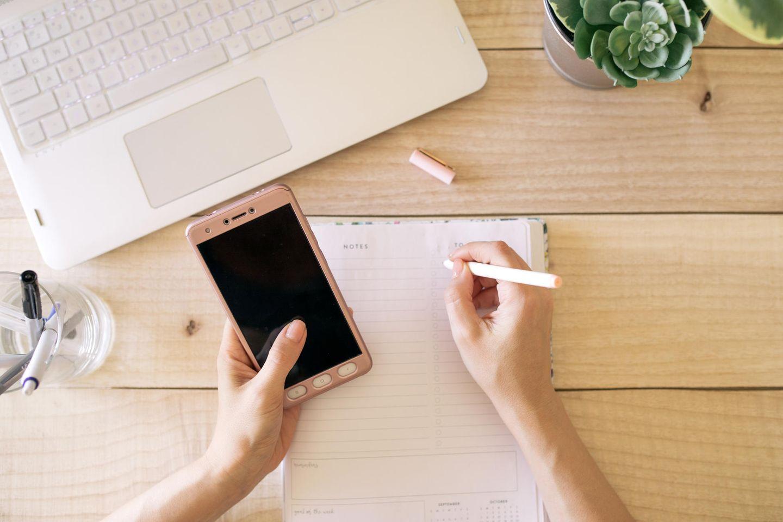 Ivy Lee-Methode: Frau hält Handy und schreibt in einen Notizblock.