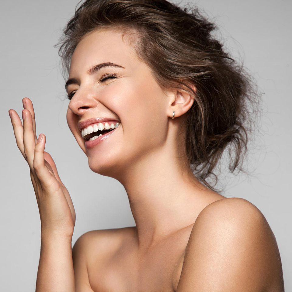 Junge Schönheit lacht und hält sich die Hand vor das Gesicht