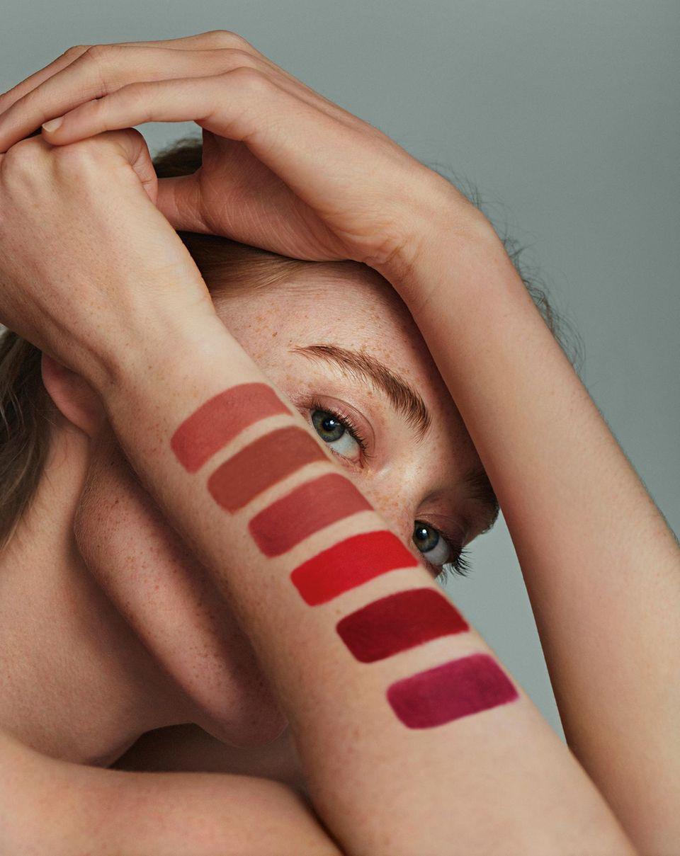 Kussmund gefällig?: Model mit verschiedenen Lippenstiftfarben am Arm