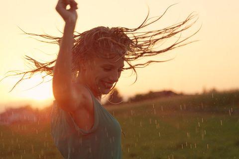 Glückliche Sternzeichen 2021: Frau tanzt im Regen