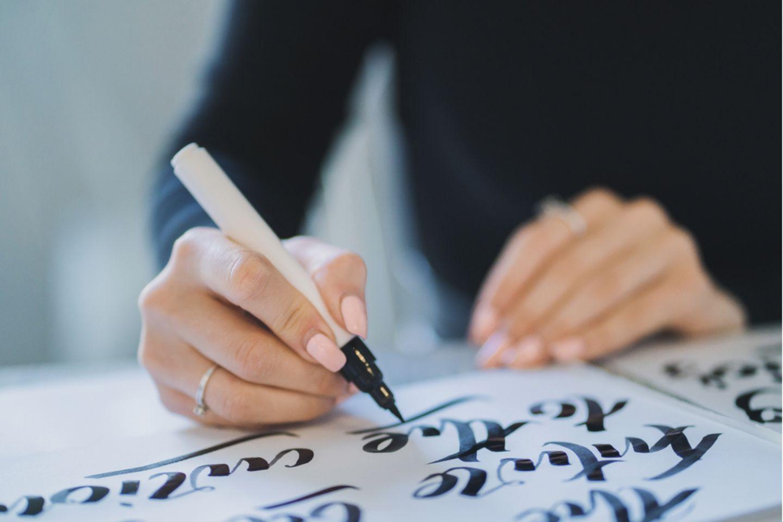 Handlettering Zahlen: Frau hält Brush Pen