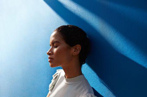 Frau lehnt an blauer Wand