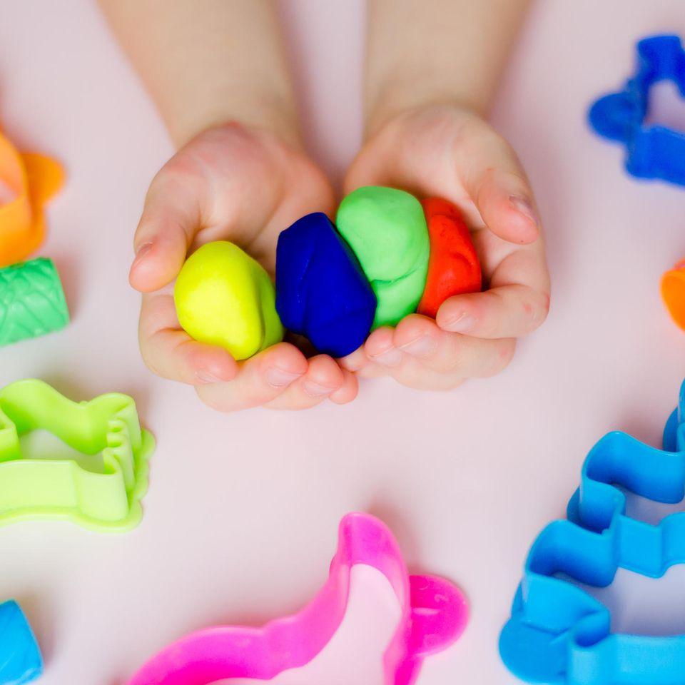 Knete selber machen: Kind mit verschieden farbiger Knete